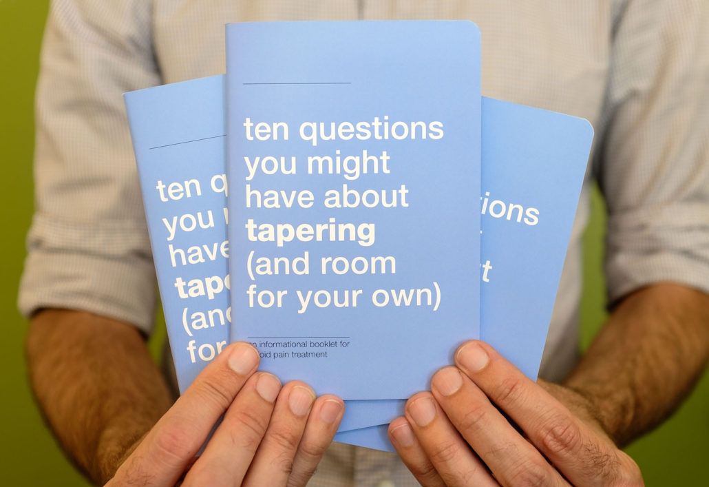 "Man holding three small blue booklets titled ""ten questions you might have about tapering (and room for your own)"""