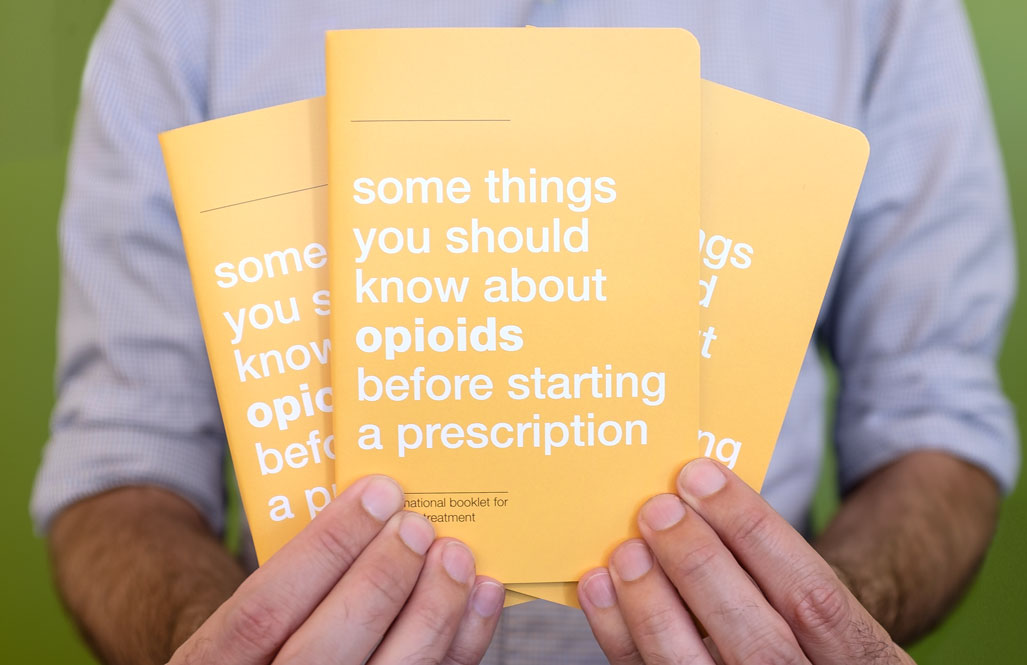 """Man holding three small yellow booklets titled """"some things you should know about opioids before starting a prescription"""""""