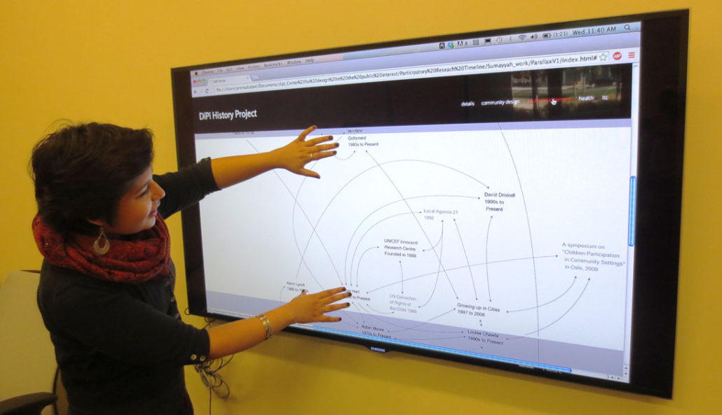 Person gesturing at interactive timeline on a large digital display.
