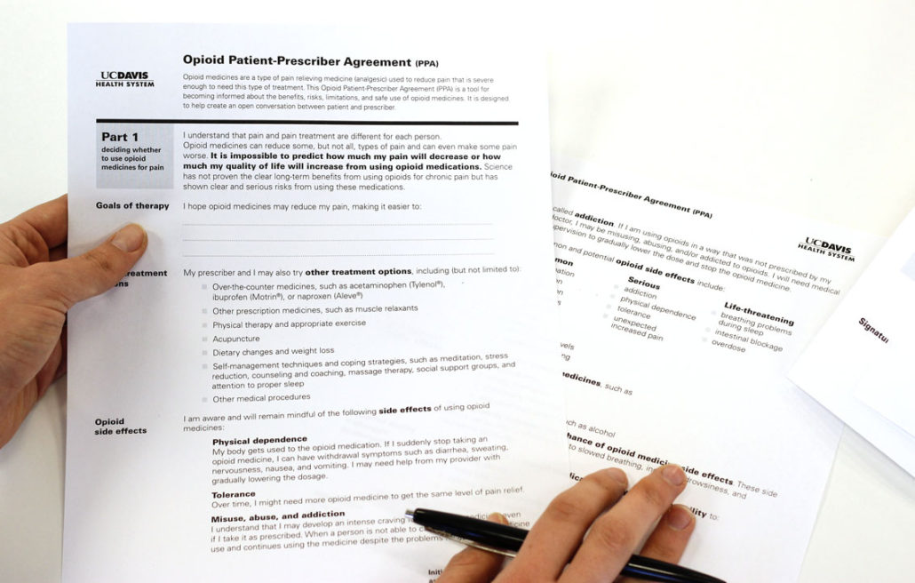 Closeup photo of the Patient Provider Agreement being held by one person holding a pen