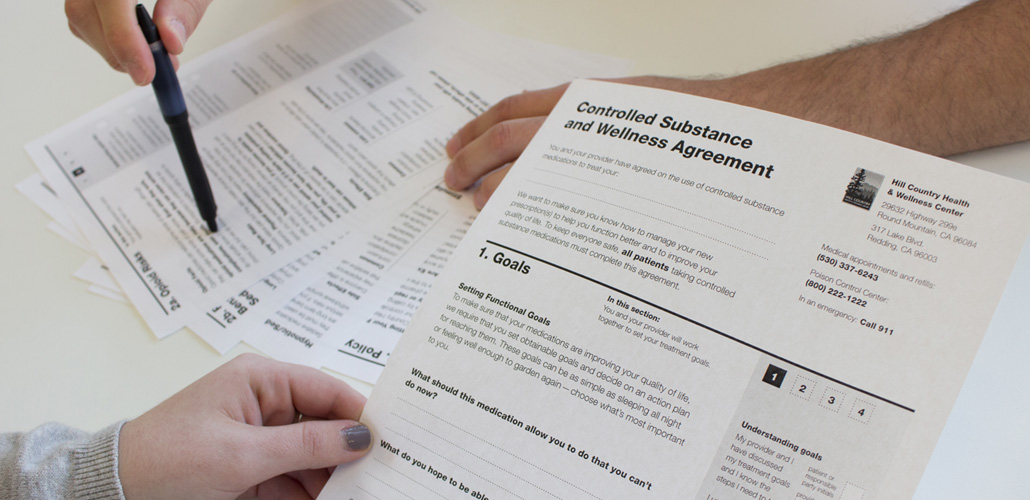 Close-up of two people's hands as they read through a Controlled Substance and Wellness Agreement document